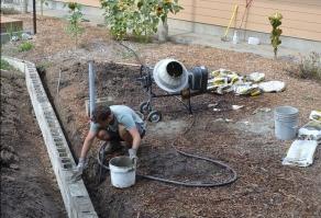 Alex pouring concrete into the cinder blocks.