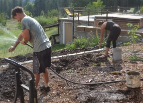 Alex and Emily working hard to finish pouring concrete into the new cinder-block retaining wall.