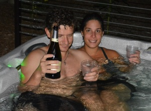Alex and Emily celebrating a good week of wwoofing with champagne in the hot tub.