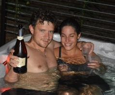 Alex and Emily celebrating the end of a hard work week with campaign in the hot tub.